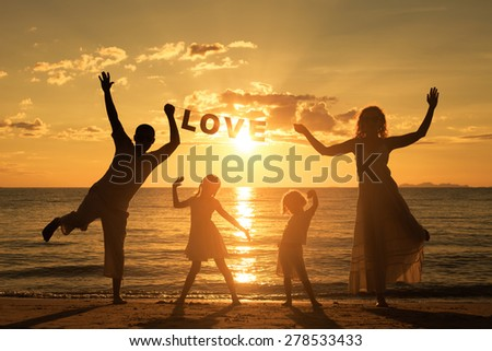 "Happy family standing on the beach at the sunset time. They keep the letters forming the word "" love"". Concept of friendly family."