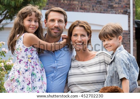 Happy family standing outside home. Cheerful happy young family outdoor. Portrait of a young family with mother, father, son and daughter looking at camera. - stock photo