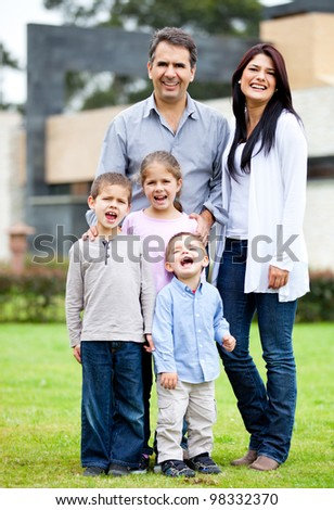 Happy family standing outside their house  and smiling