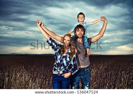 Happy family standing together in the wheat field over beautiful cloudy sky.