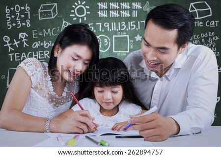 Happy family studying together on the table with scribble background on the blackboard