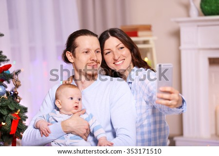 Happy family take selfie on the floor in the decorated Christmas room