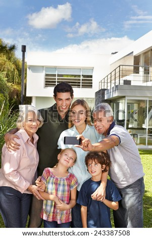 Happy family taking a selfie with cell phone in garden in front of a house - stock photo
