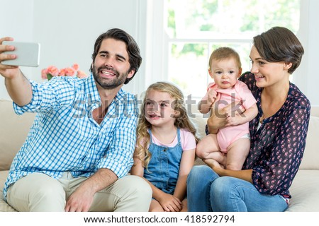 Happy family taking selfie while sitting on sofa at home