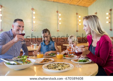 Happy family talking while having dinner at restaurant