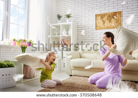 Happy family! The mother and her child girl are fighting pillows. Happy family games. - stock photo