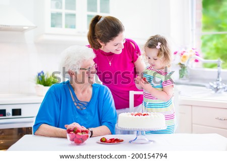 Happy family, three generations of women- senior lady, young woman and a little toddler girl baking a strawberry cake together in a white sunny kitchen with window and modern appliances - stock photo