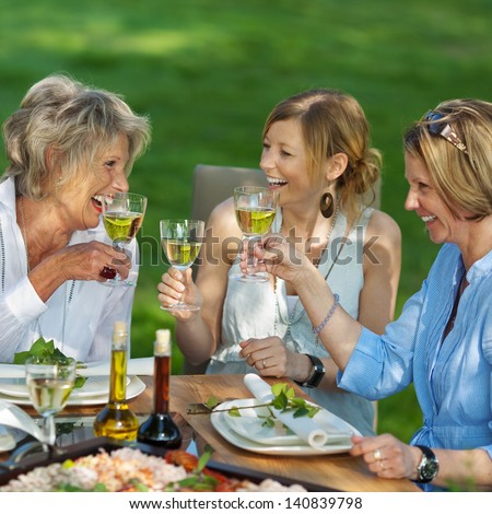 Happy family toasting white wine at dining table in lawn - stock photo