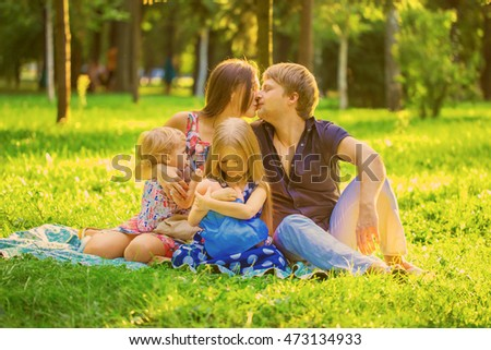Happy family together at the picnic. Mother breastfeeding baby son, little daughter is breastfeeding a doll.