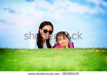 Happy family together, beautiful young mother with cute little daughter lying down on fresh green grass field in bright sunny day - stock photo