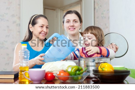 Happy family together cook  in the kitchen at home - stock photo