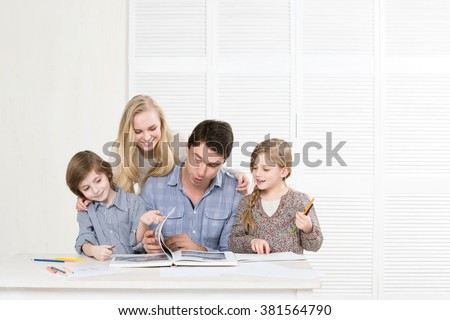 Happy family together paint and read a book. - stock photo