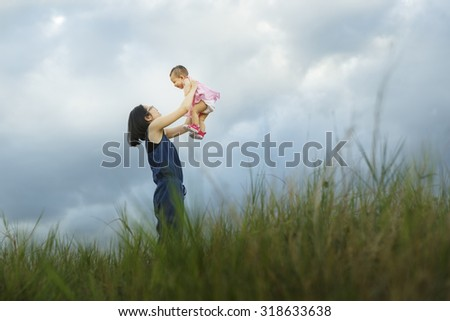 Happy family together, parents with their baby at sunset. Mother raising baby up in the air - Vibrant color effect - stock photo