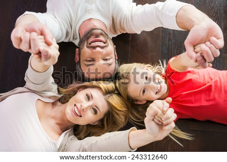 Happy family together. Top view of happy family of three bonding to each other and smiling while lying on the hardwood floor  - stock photo