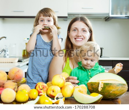 Happy family together with melon over dining table at home