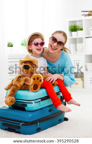 happy family tourist mother and child daughter suitcases packed for vacation - stock photo