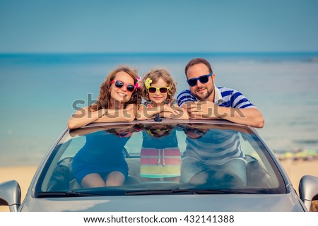 Happy family travel by car to the sea. People having fun in cabriolet. Summer vacation concept - stock photo