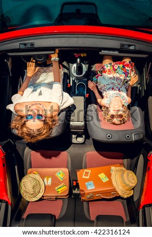 Happy family travel by car. Woman and child having fun in red cabriolet. Summer vacation and travel concept. Top view - stock photo