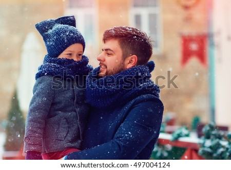 happy family under the snowfall during winter holidays