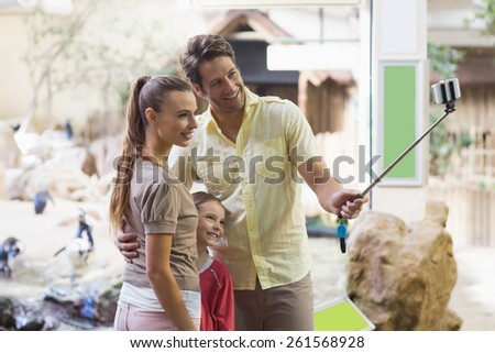 Happy family using a selfie stick at the zoo - stock photo
