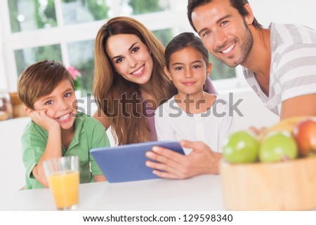 Happy family using a tablet pc in kitchen - stock photo
