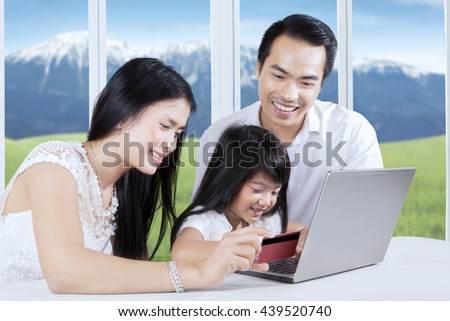 Happy family using credit card for paying online while looking at laptop computer at home - stock photo