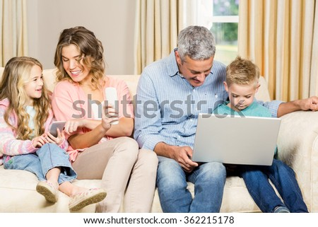 Happy family using different tech items at home