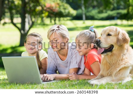 Happy family using laptop in the park on a sunny day - stock photo