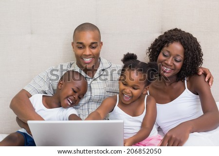 Happy family using laptop together on bed at home in the bedroom - stock photo