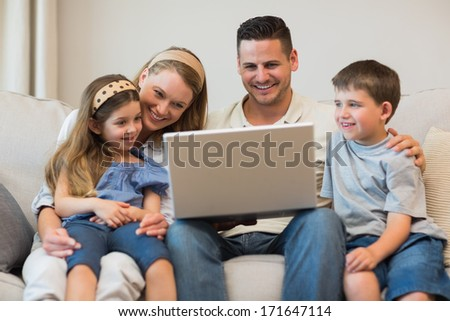 Happy family using laptop together on sofa in house - stock photo