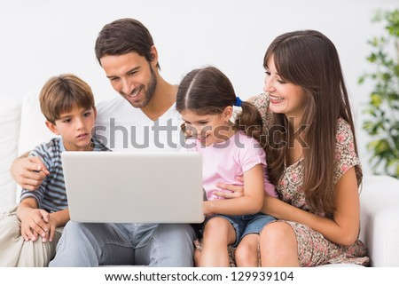 Happy family using laptop together on the couch - stock photo