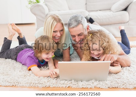 Happy family using laptop together while lying on rug at home - stock photo