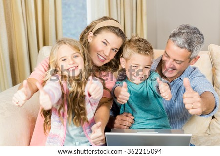 Happy family using laptop with thumbs up in living room - stock photo