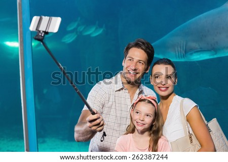 Happy family using selfie stick at the aquarium - stock photo