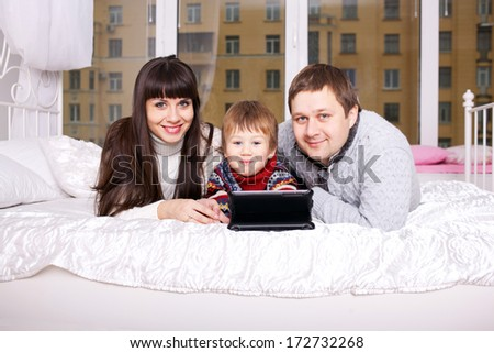 Happy family using the tablet lying on bed. Funny father, mother and child, smiling family with tablet pc looking at something and laughing. Happy family concept.