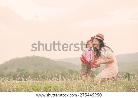 Happy family Vintage tone. A mother and son giving gift box on outdoors. Copy space - stock photo
