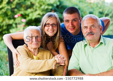 Happy family visiting the grandmother in the garden of the nursing home. - stock photo