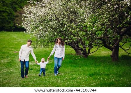 Happy family walki in the park - stock photo
