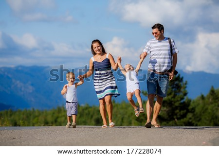 happy family walking along a mountain road - stock photo