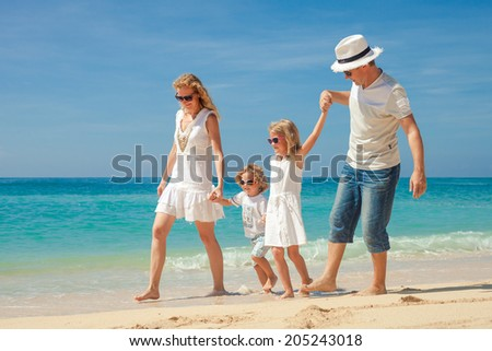 Happy family walking at the beach at the day time. Concept of friendly family. - stock photo