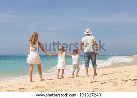 Happy family walking at the beach in the day time