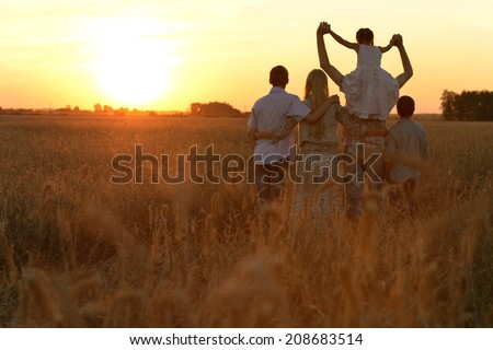 Happy family walking in field and looking at sunset - stock photo
