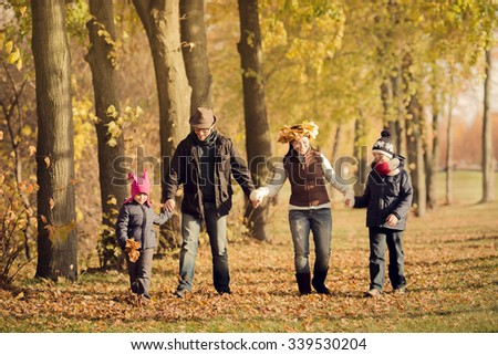 Happy family walking in the forest and holding hands all together. Parents and their children having fun during foliage. - stock photo