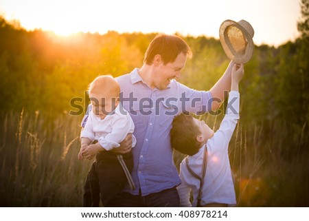 Happy family walking in the park on a sunny day. Father with adorable toddler boy and cute kid having fun on a summer meadow.  Sunset. Outdoors. Parent with children Together. - stock photo