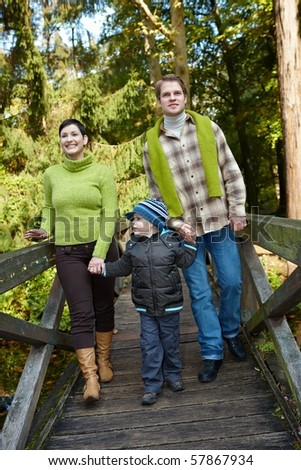 Happy family walking on bridge in autumn forest together, smiling, holding hands.? - stock photo
