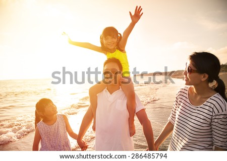 happy family walking on the beach - stock photo