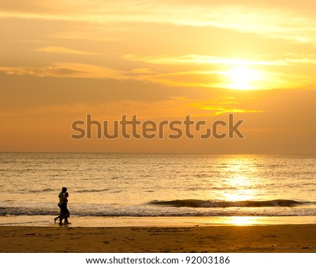 Happy family walking on the beach at sunrise for holiday time - stock photo