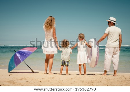 Happy family walking on the beach at the day time - stock photo