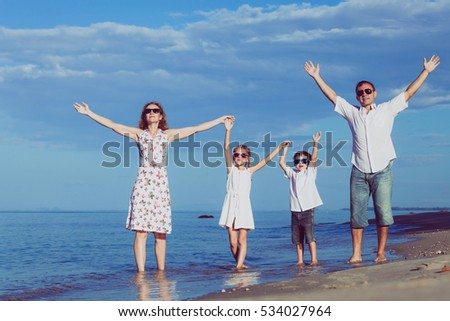 Happy family walking on the beach at the day time. People having fun on the beach. Concept of friendly family and of summer vacation.