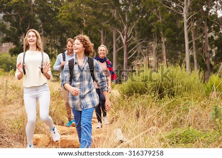 Happy family walking out of a forest - stock photo